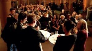 Kamera mit Blick ins Publikum über Diskussionsteilnehmer hinweg