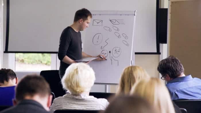 Mann an Whiteboard erklärt Dinge