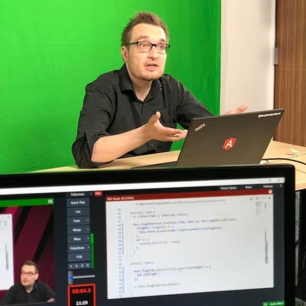 Greenscreen Studio - Redner am Rechner vor grüner Wand