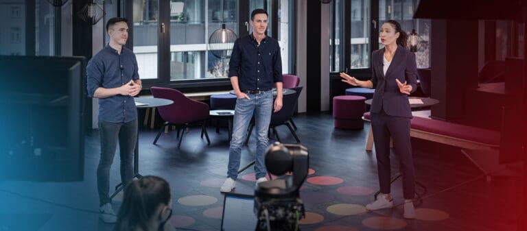 Moderatorin mit zwei Interviewpartnern spricht in die Kamera