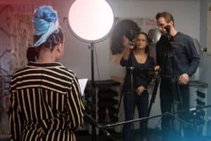 Zwei Personen an der Kamera prüfen Bildkomposition und Beleuchtung der Protagonistin