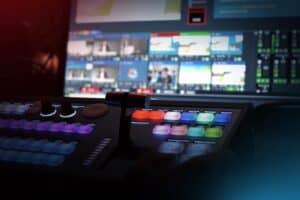 Symboldbild Streaming mit unscharfem Bildschirm im Hintergrund und Bildmischungs-Steuergerät im Vordergrund