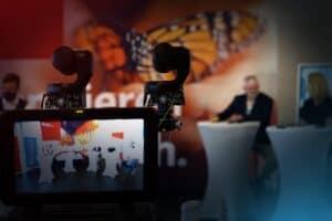 Zwei Kameras von hinten - in der Unschärfe weiter weg das Podium der Redner