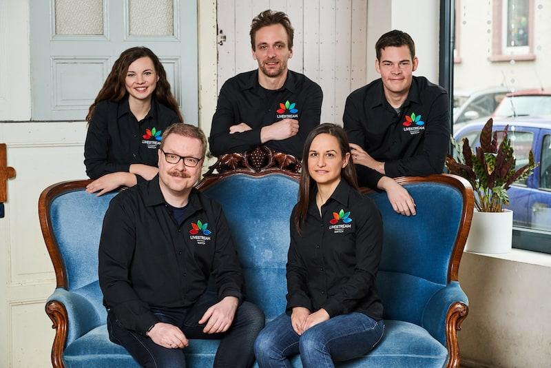 Teamfoto Livestream.watch mit Geschäftsführung auf blauem Sofa und drei MitarbeiterInnen dahinter