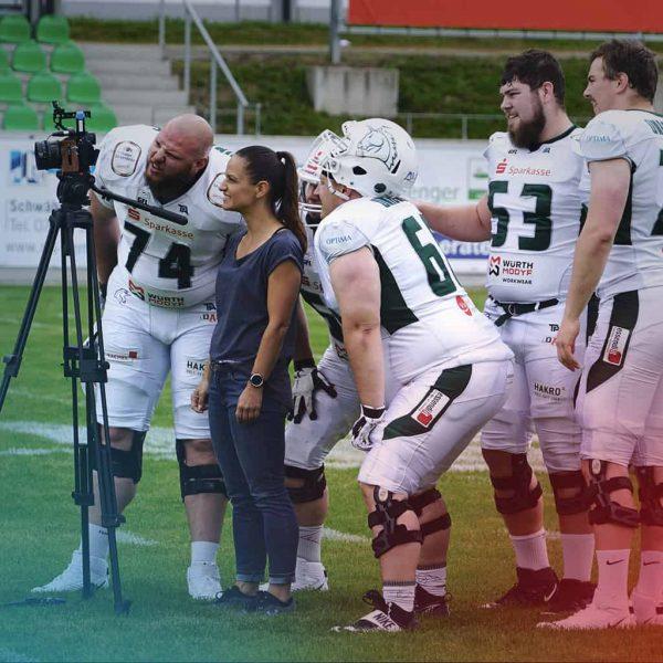 Yvonne Schulze umringt von Football-Spielern, die ihr kritisch über die Schulter schauen und das Kamerabild kontrollieren
